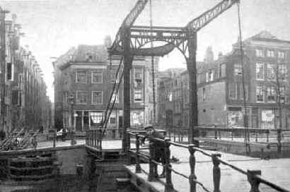 De brug over de Rapenburgerwal, links de Uilenburgerstraat, rechts de Batavierstraat. Het blok huizen tussen die straten is verwijderd. De ruimte die toen ontstond werd gebruikt voor de Nieuwe Uilenburgerstraat, en is ook de reden dat er voor de Uilenburgersjoel een voorplein is. De pakhuizen links in de Uilenburgerstraat staan er nog.